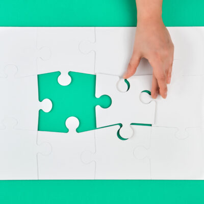 hand holds the missing element in the game of puzzles on a green background